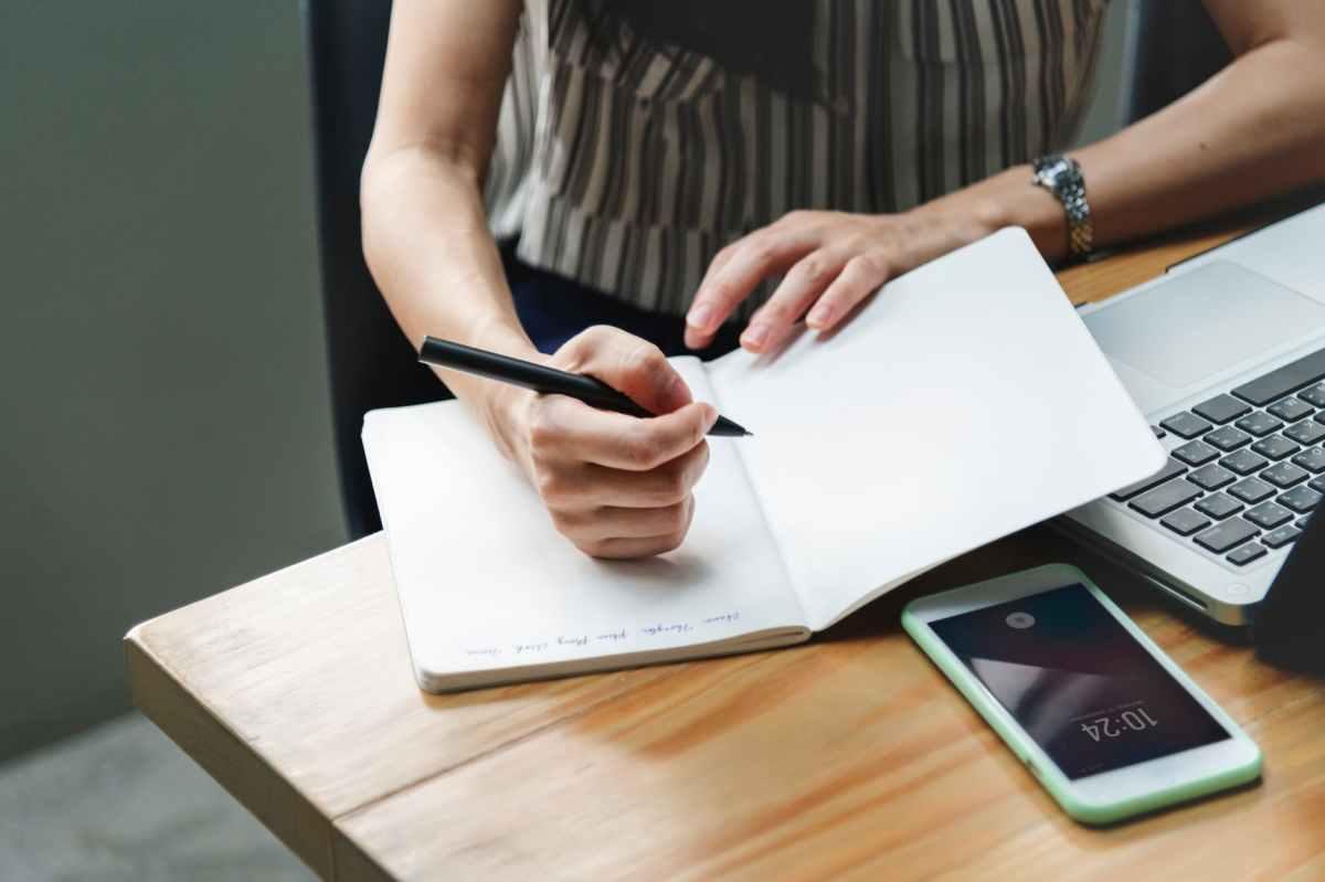woman holding pen beside laptop